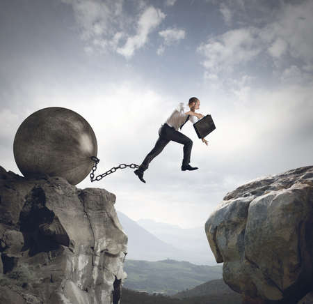 Businessman jumps the obstacle with the weight Stockfoto