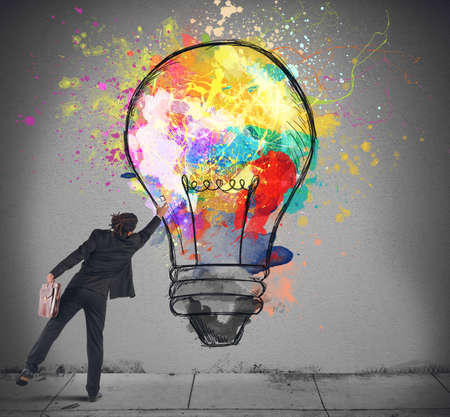 Businessman color with a spray a lightbulb photo