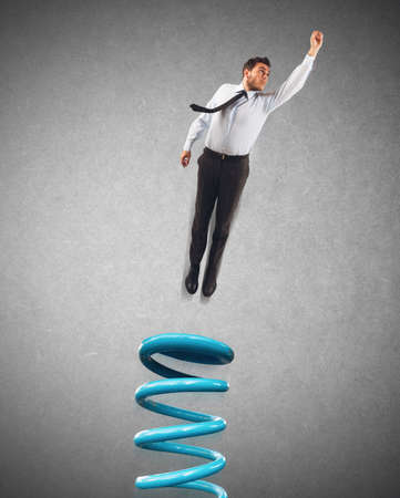 people force: Businessman uses a spring to make leap Stock Photo