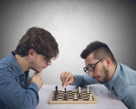 business mind: Two brothers play and compete in chess game