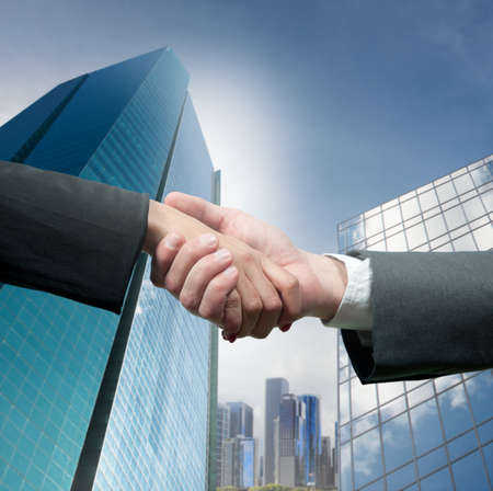 highrise: Business people shaking hands over a deal