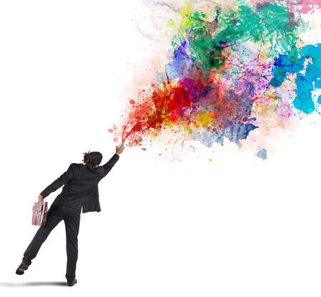 Young and creative businessman colors with spray Stock Photo