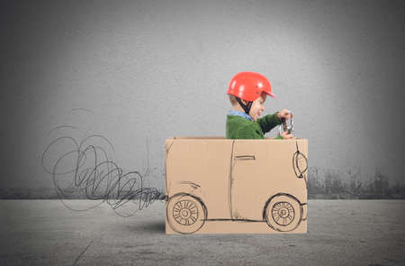 Creative baby plays with his cardboard car Фото со стока