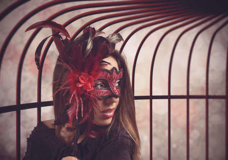 Seductive woman hides with a mysterious mask photo