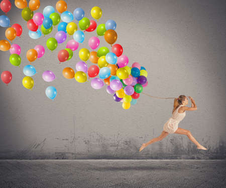 carefree: Carefree and happy girl jumping with balloons Stock Photo