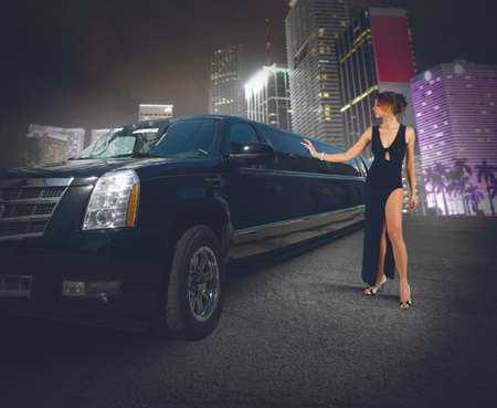 Rich woman touches and admires her limousine photo