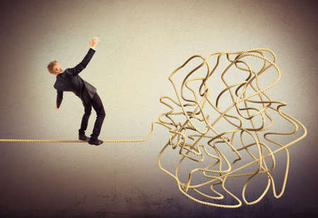 attempts: Businessman balancing attempts to get to tangle