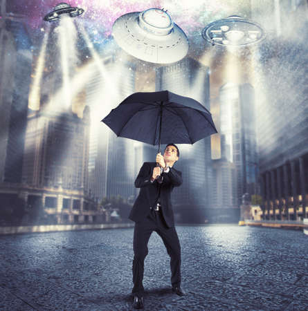 space invader: Businessman protects himself from an alien attack Stock Photo