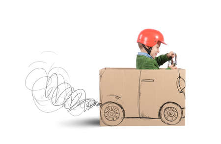 fun: Creative baby plays with his cardboard car Stock Photo