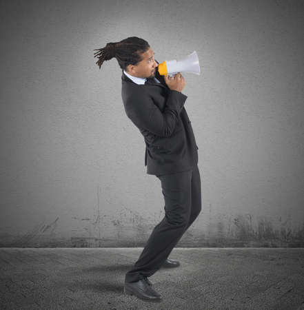 tries: Businessman fearful tries to use the megaphone Stock Photo