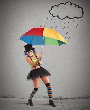 sheltering: Clowns with rainbow umbrella sheltering from rain Stock Photo