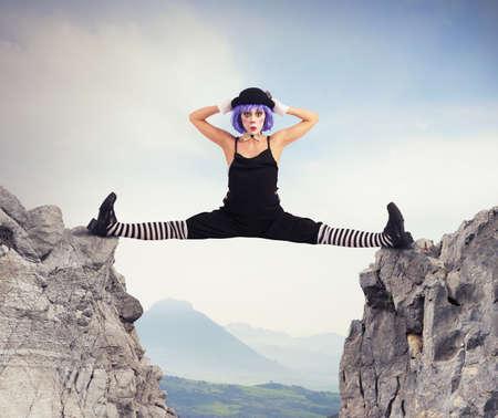 Clown danser maakt split tussen twee bergen Stockfoto