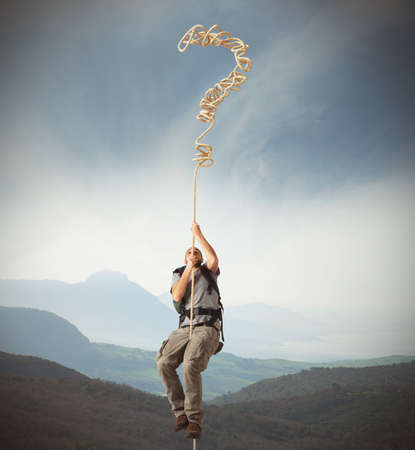 problems solutions: Explorer clinging to a rope of interrogative Stock Photo