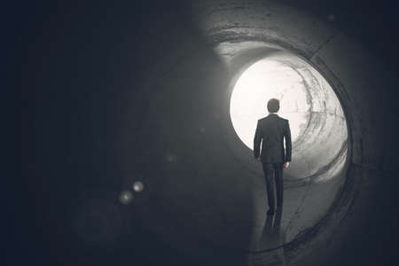stress: Determined businessman gets out of the tunnel