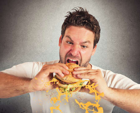 eager: Man eating a sandwich with violent impetuosity