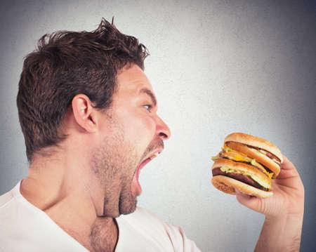 comiendo: Hombre insaciable hambre y comiendo un s�ndwich Foto de archivo