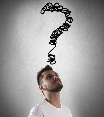 interrogativa: Muchacho con una gran pregunta en la cabeza Foto de archivo