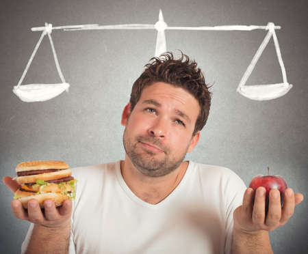 unhealthy diet: Man choosing between healthy food and unhealthy