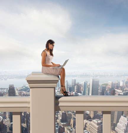 Vrouw die bij pc ontspannen boven de stad