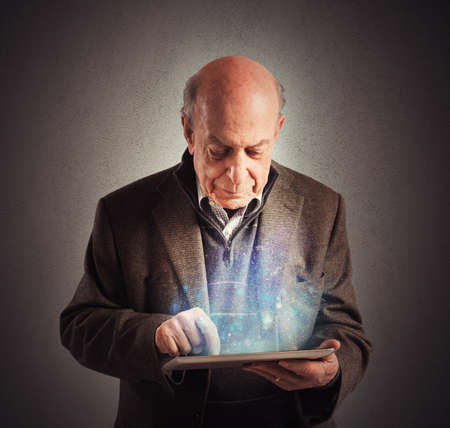 social care: Senior uses tablet to surf the internet Stock Photo