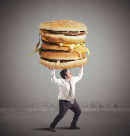 unhealthy lifestyle: Fat man supports the weight of sandwich Stock Photo