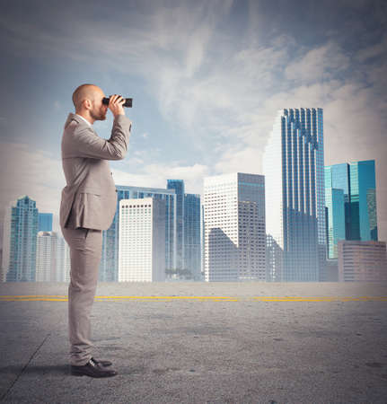 Businessman observes from a distance with binoculars