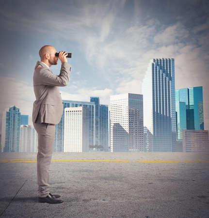 El hombre de negocios observa desde la distancia con binoculares Foto de archivo - 38004223