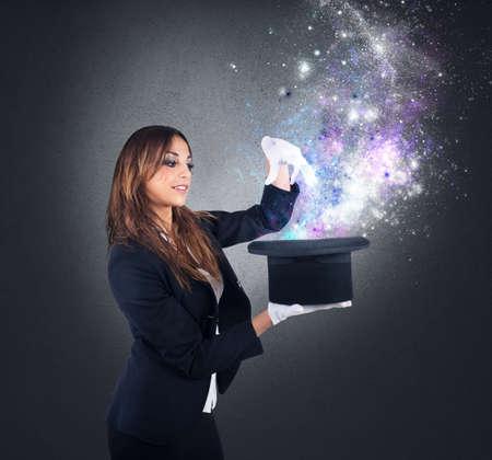 alzando la mano: Mujer mago hace magia con su sombrero