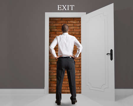 arduous: Businessman in front of an exit hampered