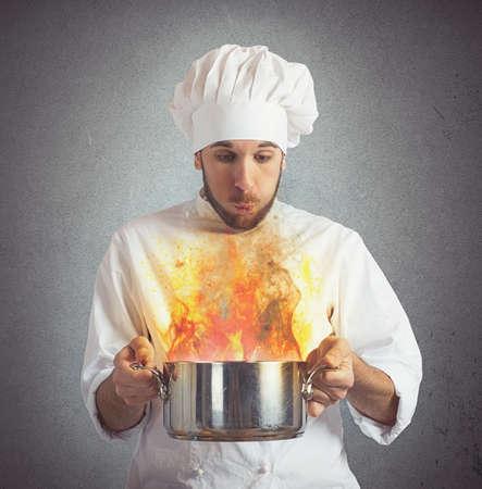 シェフが鍋で彼の焦げた食品を吹いて