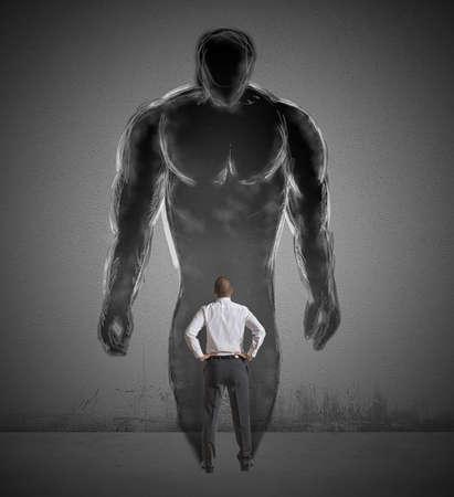Concepto de determinación con un hombre de negocios y una fuerte sombra Foto de archivo