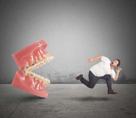 cure prevention: Man runs away for fear of dentist Stock Photo
