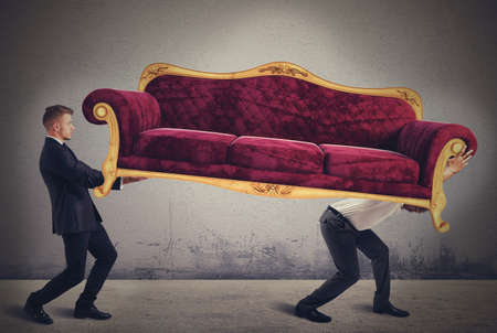 overloaded: Men carrying a very heavy antique sofa Stock Photo