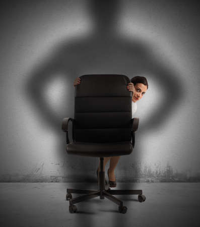 Businesswoman frightened by her pissed boss hides Stock Photo