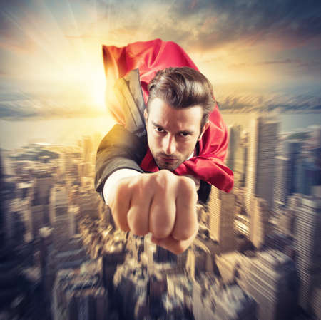 Businessman superhero flies faster in the sky Stock Photo