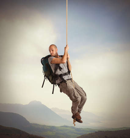 Explorer with vertigo hanging from a rope Imagens
