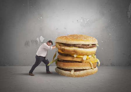 다이어트에서 뚱뚱한 사람이 건강에 해로운 샌드위치를 푸시합니다. 스톡 콘텐츠