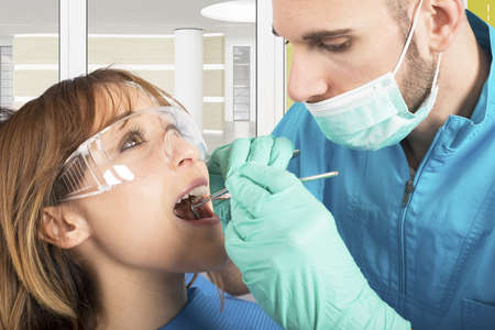 caries dental: Dentista efect�a una limpieza de los dientes