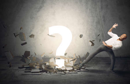 indecision: Businessman frightened by a big question point Stock Photo