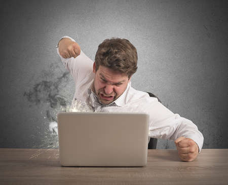 Stressed businessman breaks the computer with punch Stock Photo