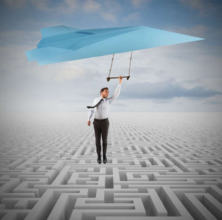 escapes: Businessman escapes from a maze flying away Stock Photo