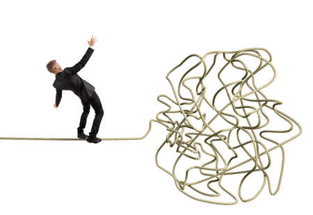 financial obstacle: Businessman balancing attempts to get to tangle