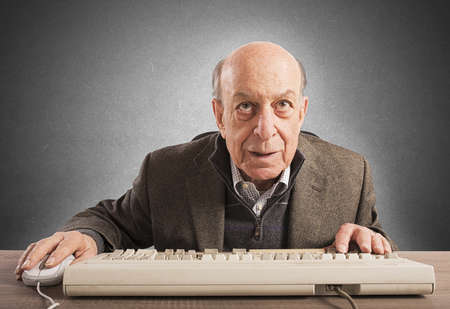 monitor de computadora: Trabajo empollón mayor con su teclado de la vendimia Foto de archivo
