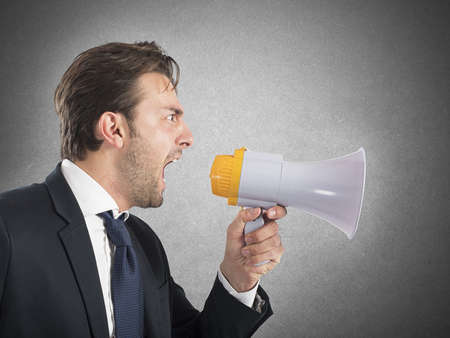 his: Angry business boss shouting with his megaphone