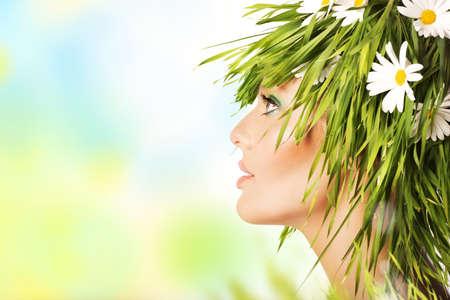 新鮮な草の髪とカモミールの花と自然の美しさの女性