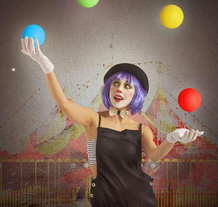 Geconcentreerde jongleur clown spelen met kleurrijke bal Stockfoto