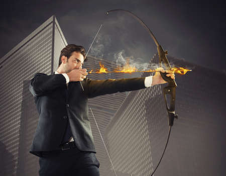 Determinated businessman with flaming arrow takes aim Reklamní fotografie