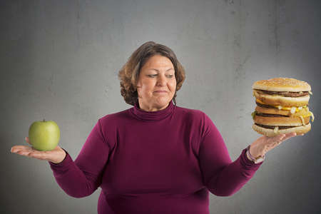 whether: Woman undecided whether to start the diet Stock Photo