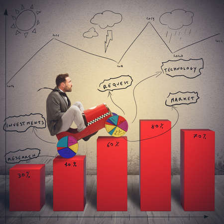 uphill: Businessman driving uphill in difficult economic landscape