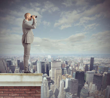 opportunity discovery: Curious businessman looks beyond with his binoculars
